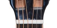 Nut einer akustischen Gitarre; bei diesem Instrument besteht die Nut aus weißem Kunststoff