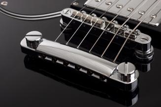 Tailpiece und Steg einer elektrischen Gitarre. Die Saiten laufen jede über einen eigenen einstellbaren Steg. Die Stege sitzen auf einer gemeinsamen Konstruktion, die ihrerseits für eine korrekte Saitenlage exakt eingestellt werden kann. (Fotolia)
